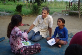Children study English using the <i>Ollie the Elephant</i> books, at one of the slums in India where Charity United's educational programs are in operation.